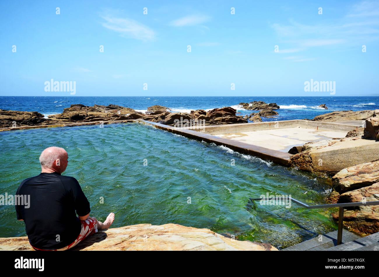 Man sitting on edge of pool at the Blue Pool Bermagui NSW Australia - Stock Image