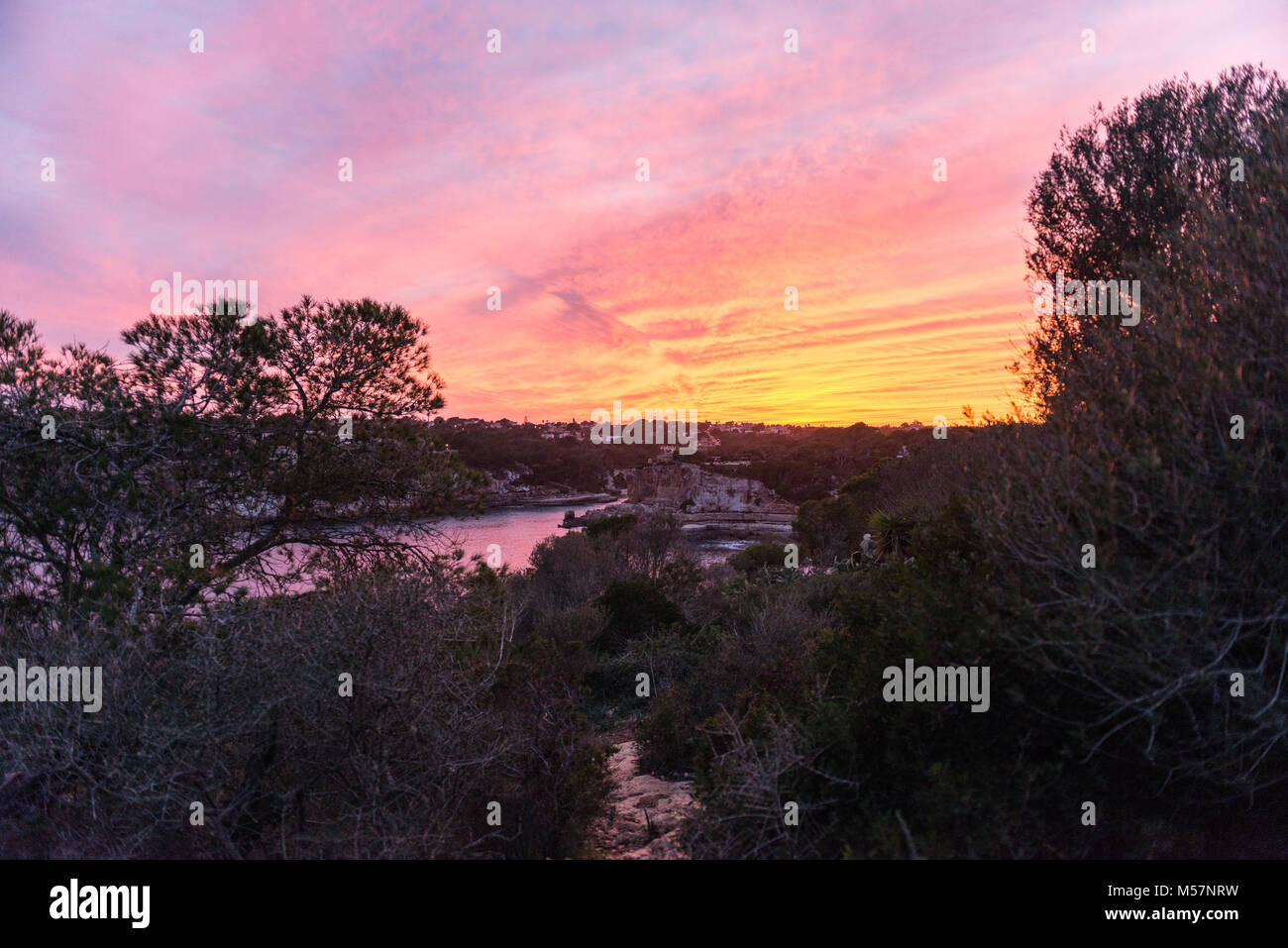View of a colorful sunset over Cala Llombards in Mallorca, Spain. - Stock Image