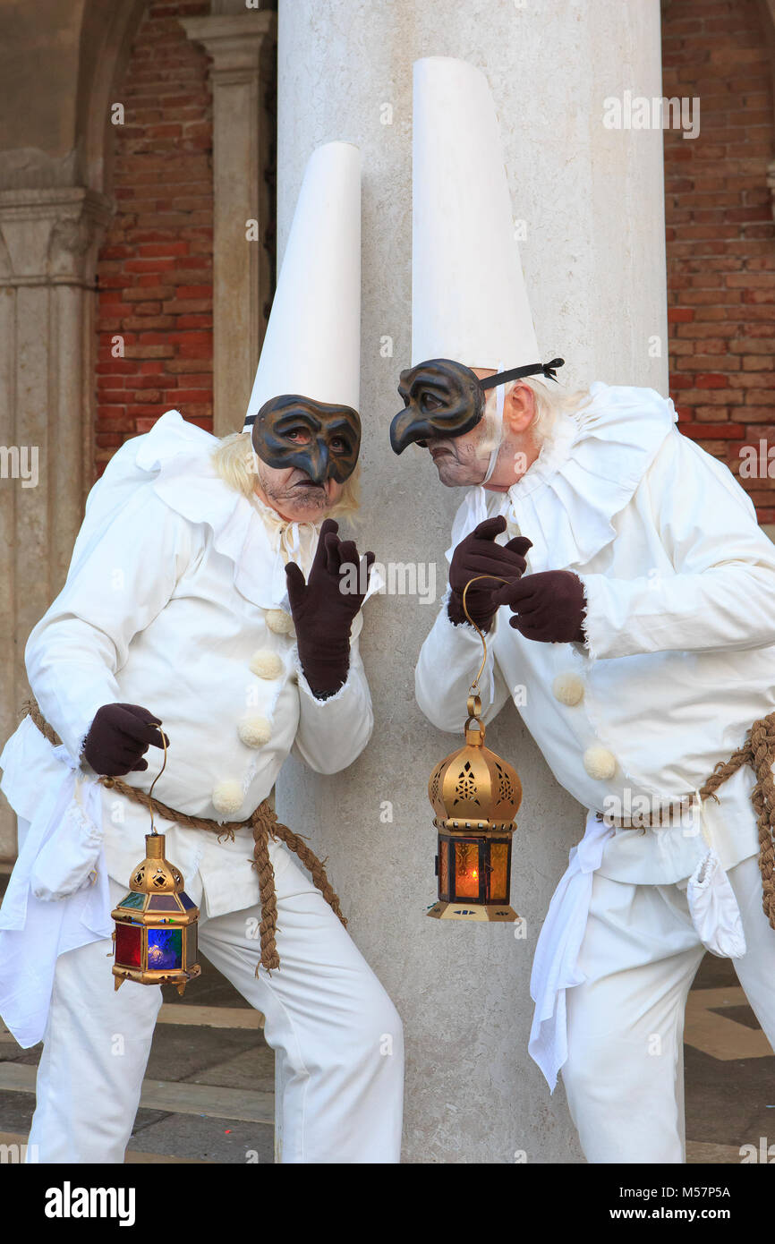 Two old masked men whispering secrets outside the Doge's Palace during the Carnival of Venice (Carnevale di - Stock Image