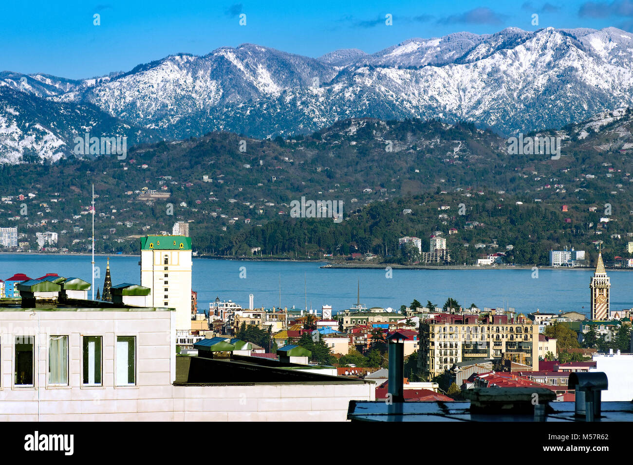 Picturesque view of the city, the roofs of the houses, the sea, the mountains covered with snow. Close up to nature. - Stock Image