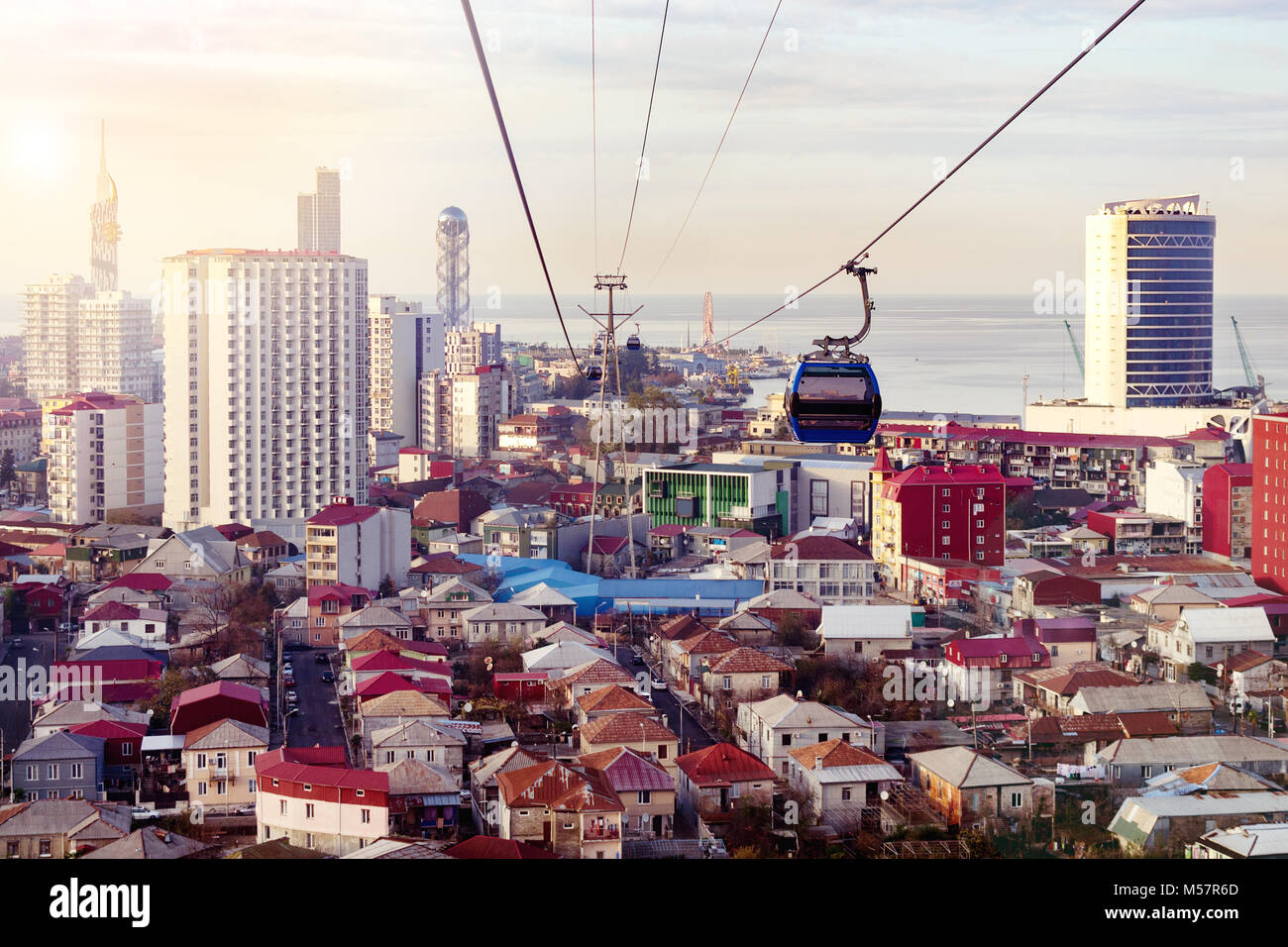 Aerial cableway above city roofs of Batumi, Georgia. Urban landscape with high-rise and ordinary single storey houses - Stock Image
