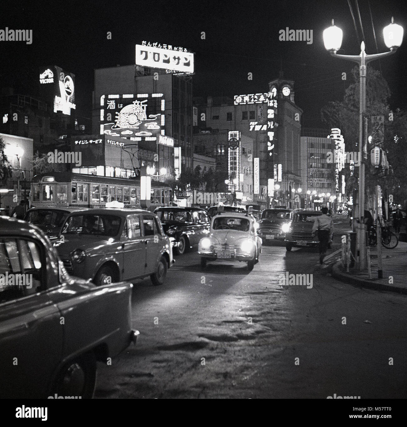 Tokyo, Japan, 1950s, historical picture showing the neon lighting of the city in the evening with the streets busy - Stock Image