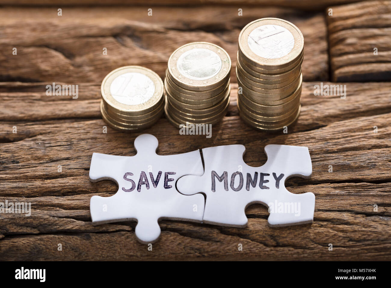 Closeup of save money jigsaw pieces by stacked coins on wood