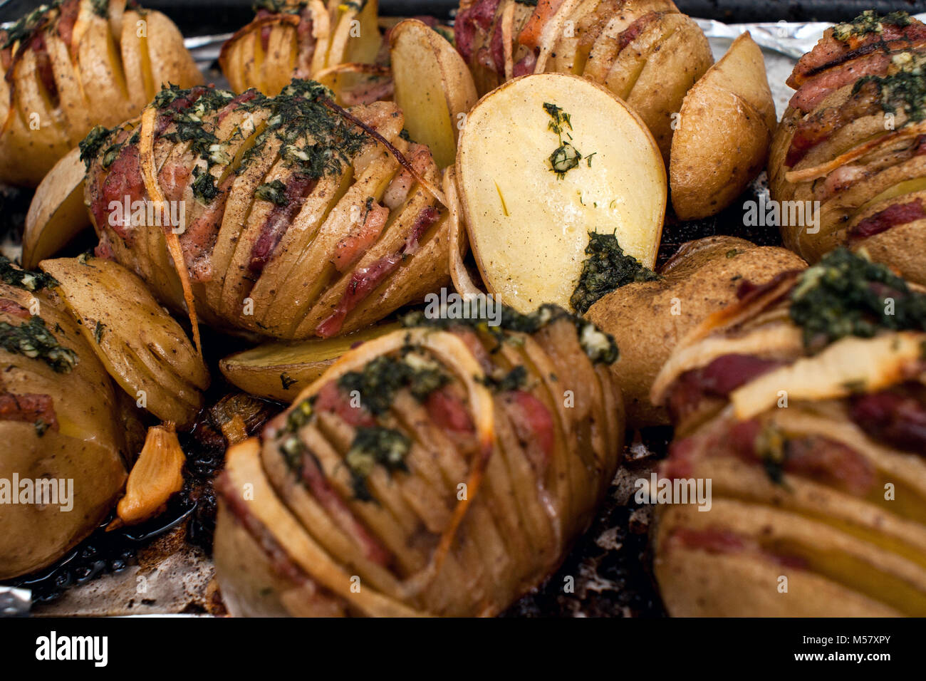 Potato.Roasts potatoes. Home cooking. Baking pan full of baked potatoes stuffed with bacon sausage onions and grated Stock Photo