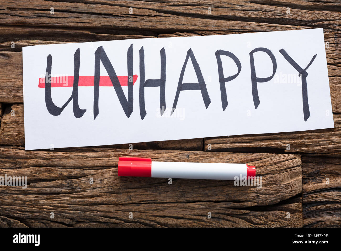 Closeup of unhappy word on paper with strike on un text by marker on wood Stock Photo