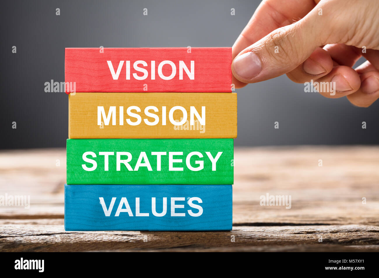 Closeup of hand building colorful blocks of vision mission strategy and values on wood - Stock Image