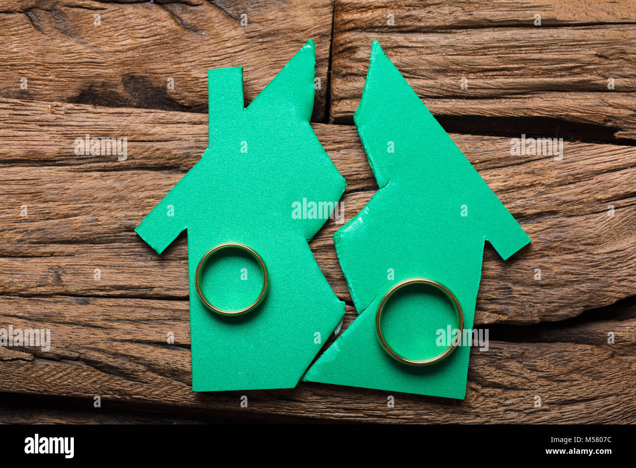 Closeup of rings on broken model house on wood representing relationship difficulties - Stock Image