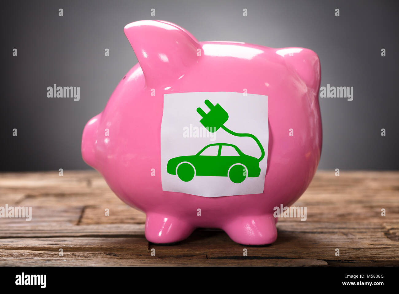Closeup of green electric car on pink piggybank on wood Stock Photo