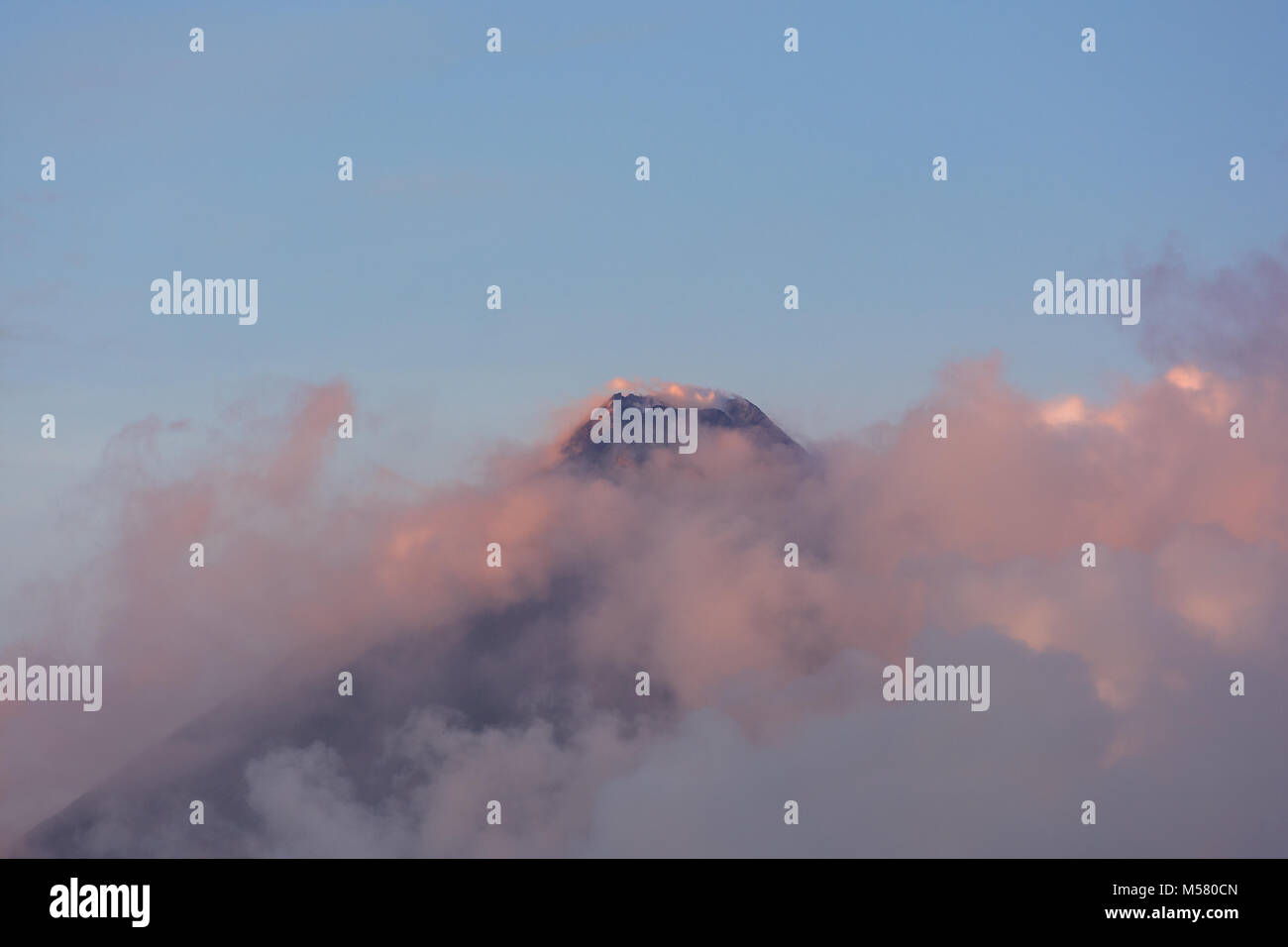The tip and creator of Mt Mayon on the island of Luzon in the Philippines surrounded by clouds and lite by the morning - Stock Image