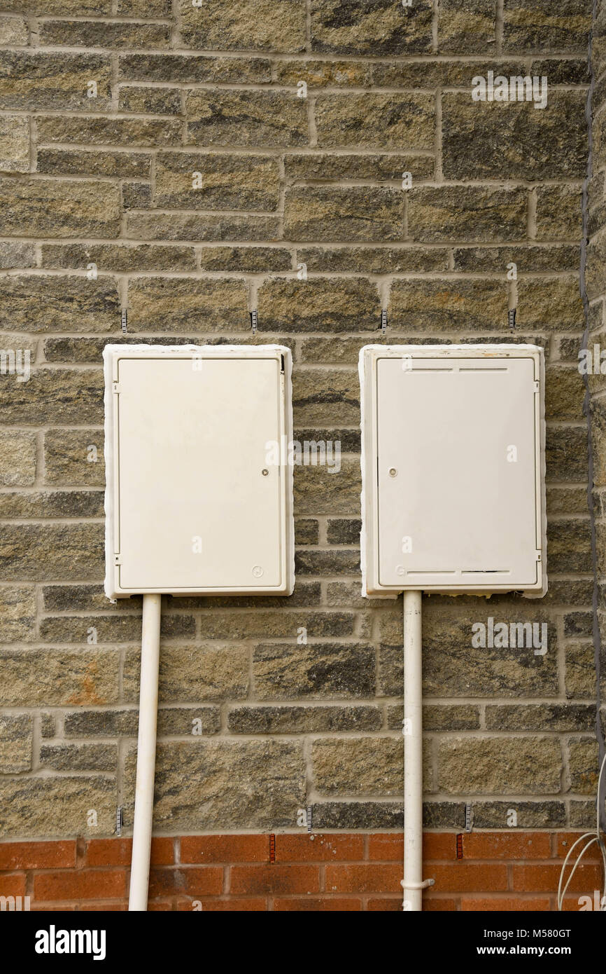White plastic utilities boxes on a newly built home - Stock Image