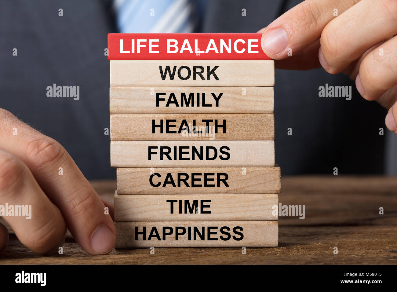Closeup of businessman building life balance concept with wooden blocks on wood - Stock Image