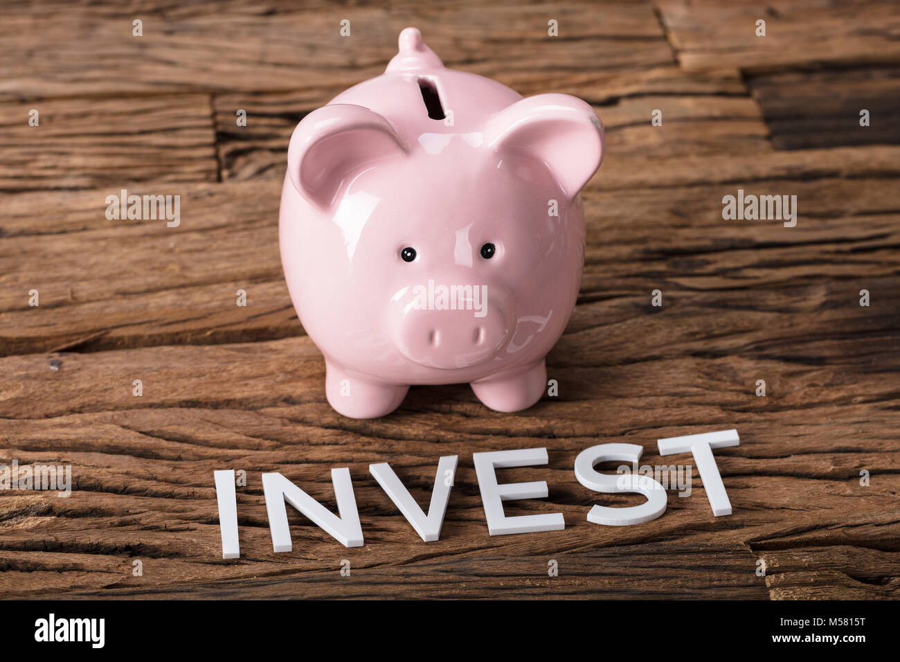 Closeup of pink piggybank by invest text on wooden table - Stock Image