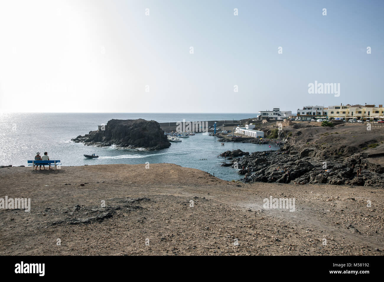 View of the small habour of village El Cotillo, Fuerteventura, Canary Islands, Spain. A small boat leaving the habour, Stock Photo
