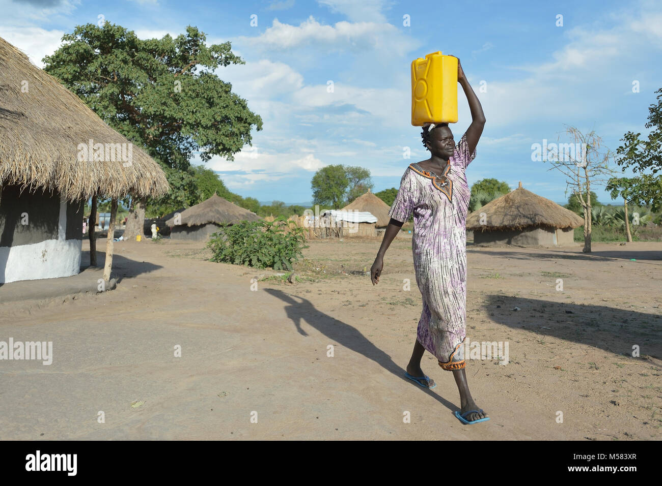 A Dinka woman from South Sudan carries water in the Rhino Refugee Camp in northern Uganda. - Stock Image