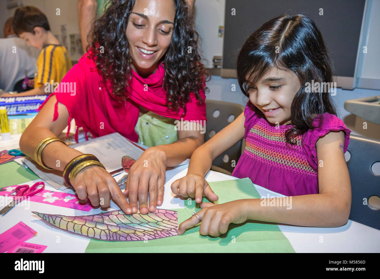 family workshop 3 D model design creativity Middle Eastern woman mother parent girl glue construction paper arts - Stock Image