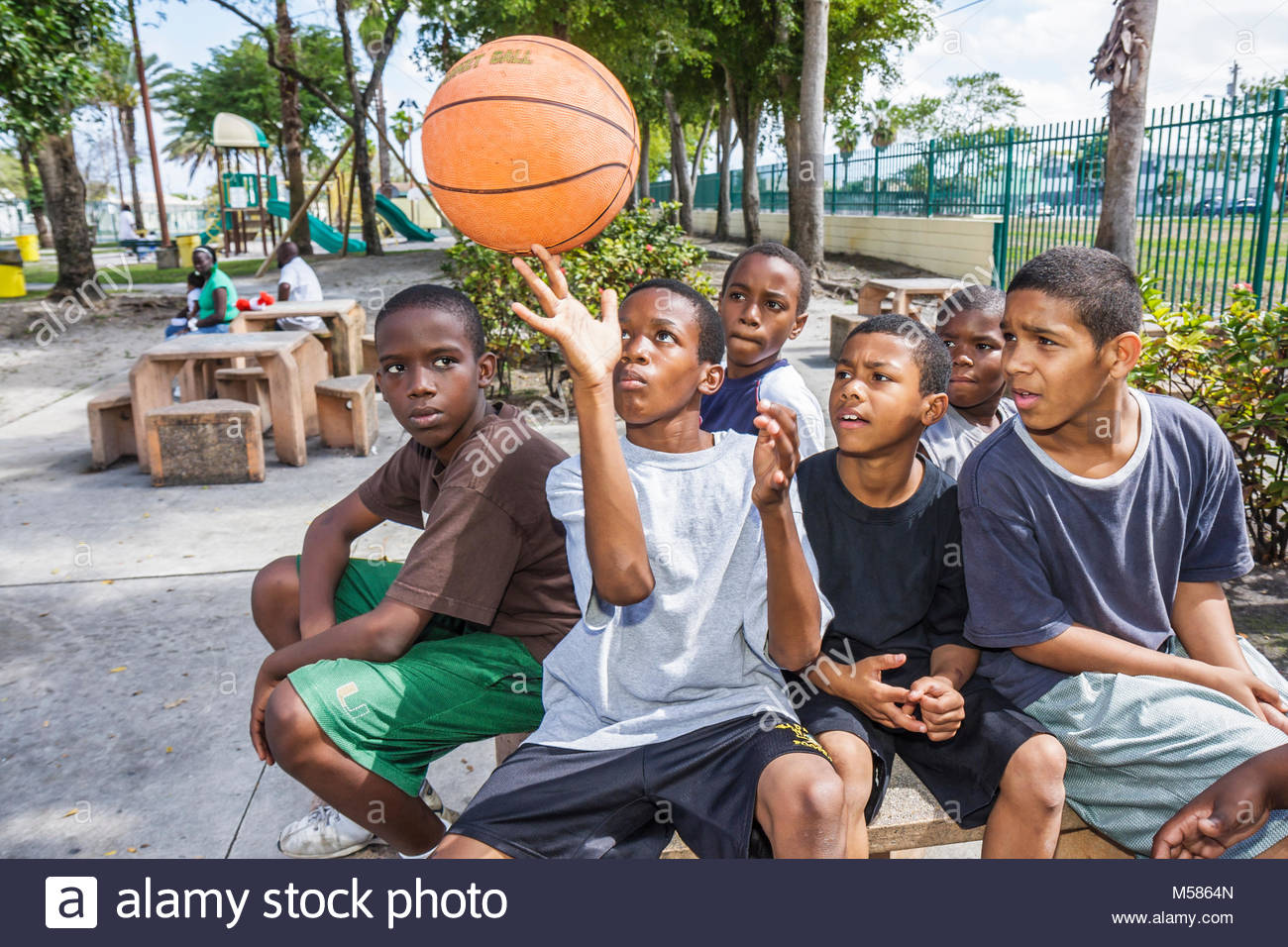 Black boys group[ park playground show off demonstrate skillful basketball play balance spin - Stock Image