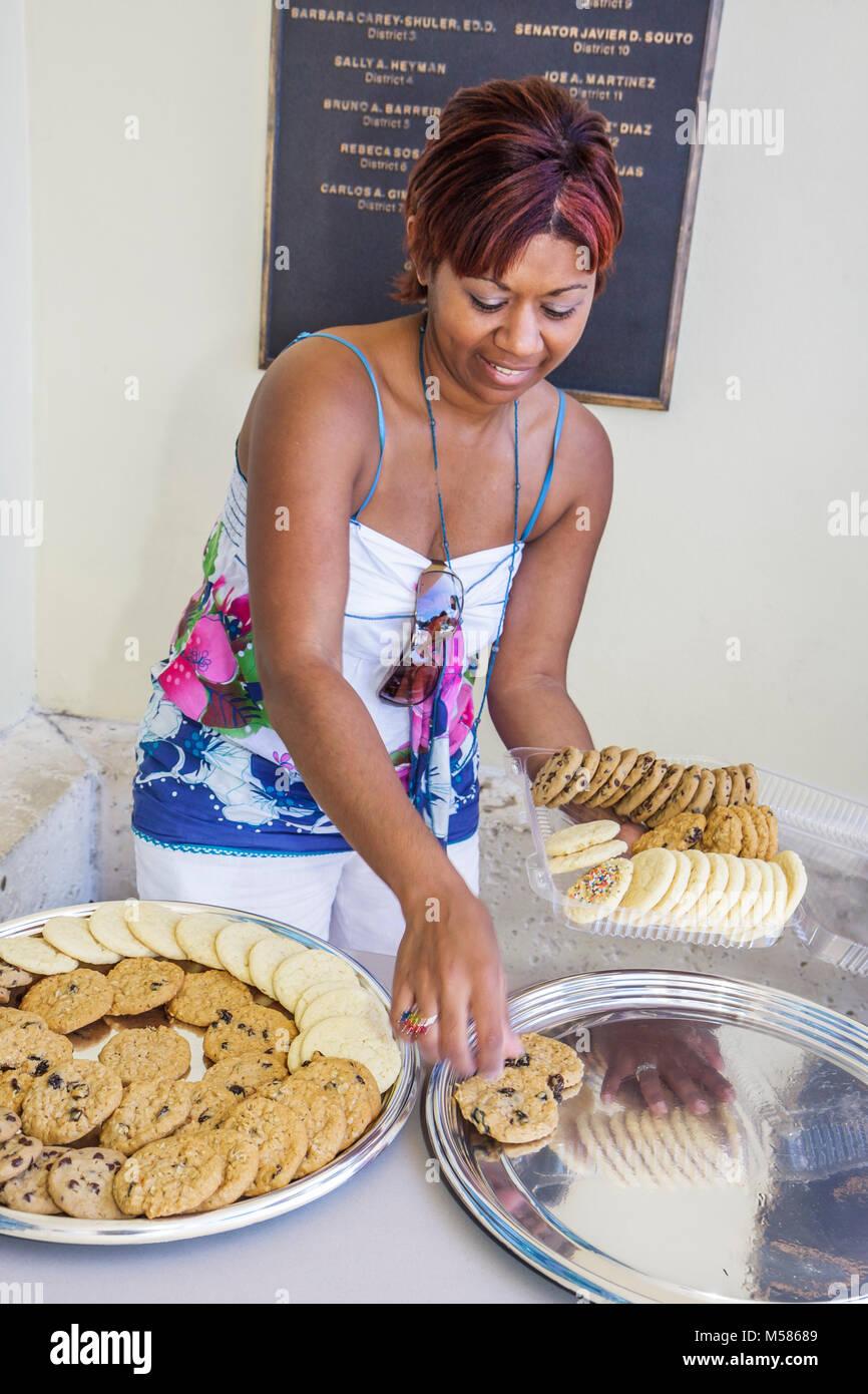 Black woman cookies platters desert sweets arranging display - Stock Image