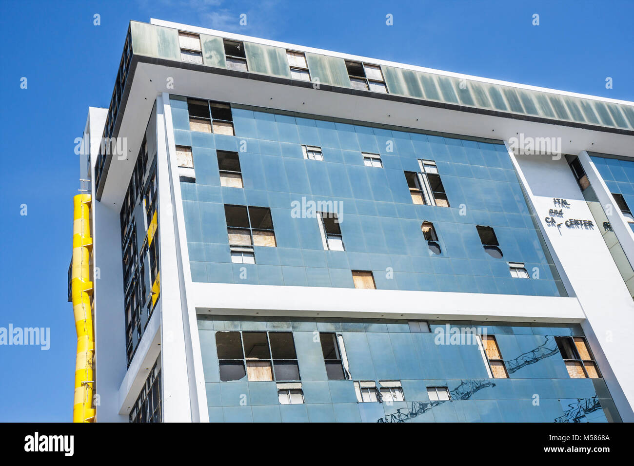 high rise building former South Shore Hospital hurricane damage boarded up windows broken glass panels commercial - Stock Image
