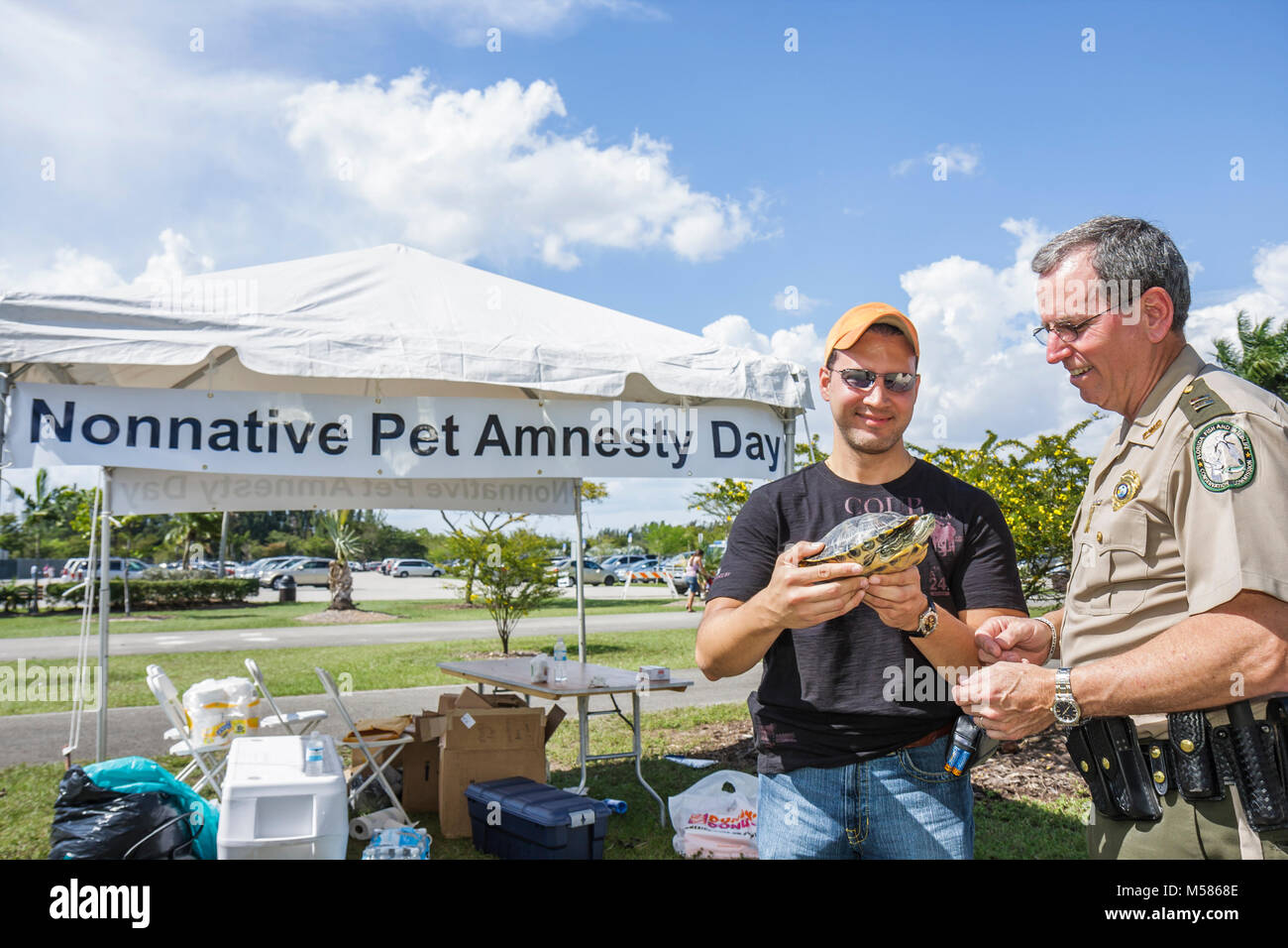 Miami Metrozoo Nonnative Pet Amnesty Day law enforcement uniformed officer tent red slider turtle - Stock Image