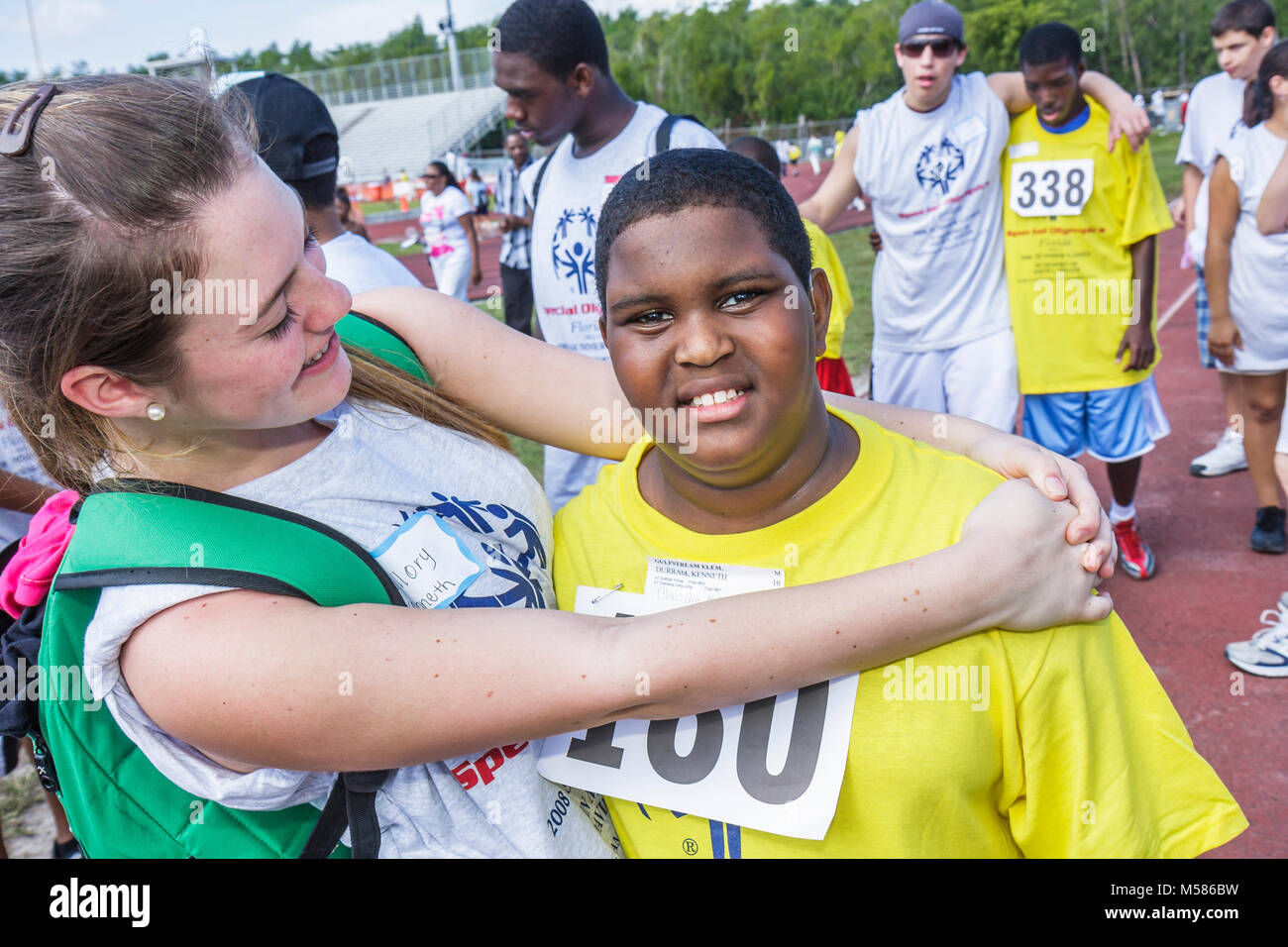 Special Olympics mentally physically disabled competition volunteers student sport teen female hugging Black boy - Stock Image