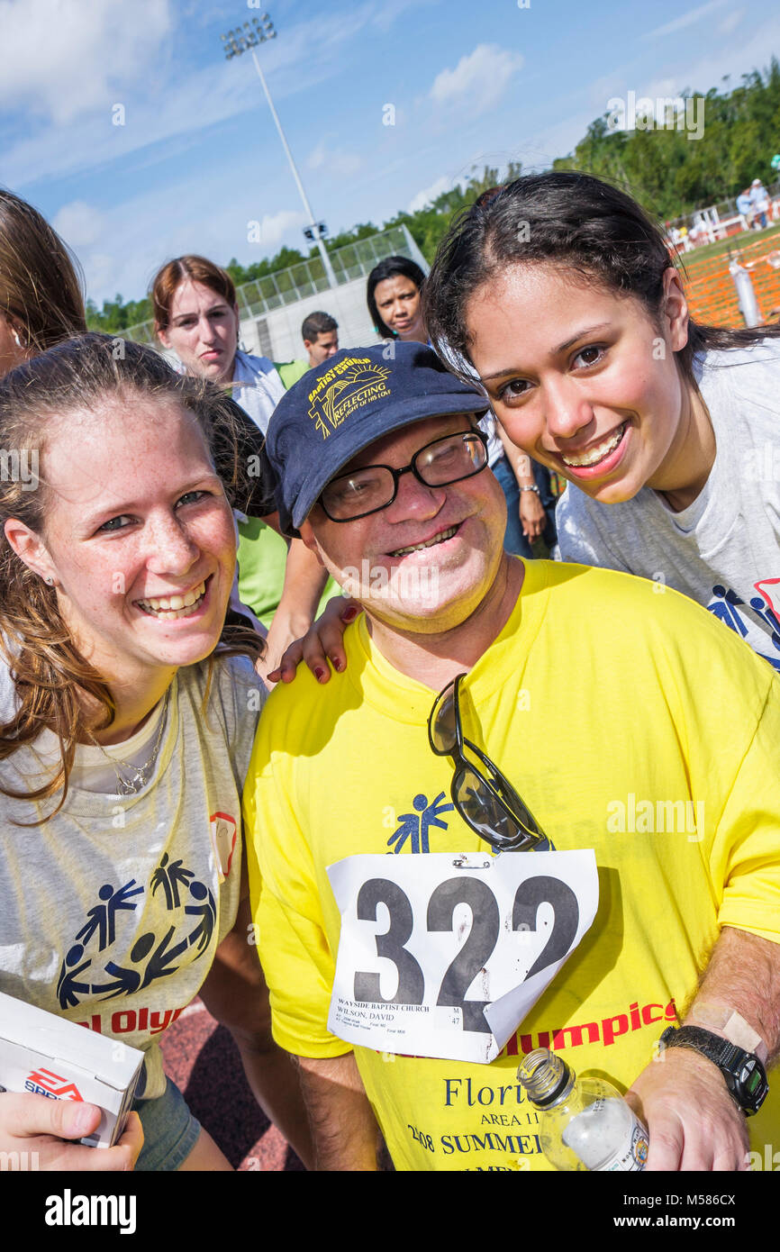 Special Olympics mentally physically disabled competition volunteers student sport Hispanic female man - Stock Image