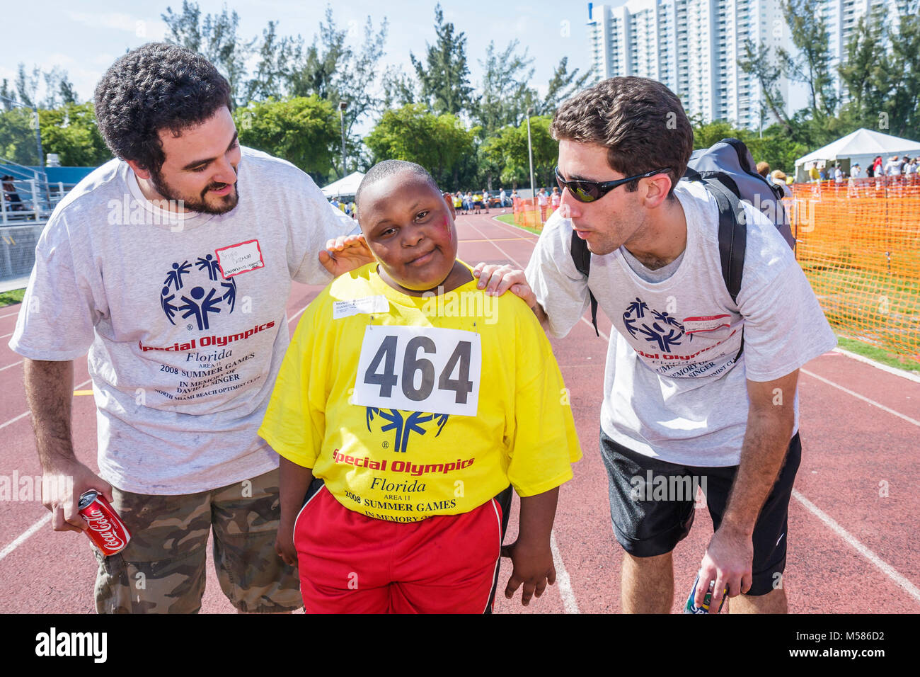 Special Olympics mentally physically disabled competition volunteers student sport Hispanic male Black boy - Stock Image