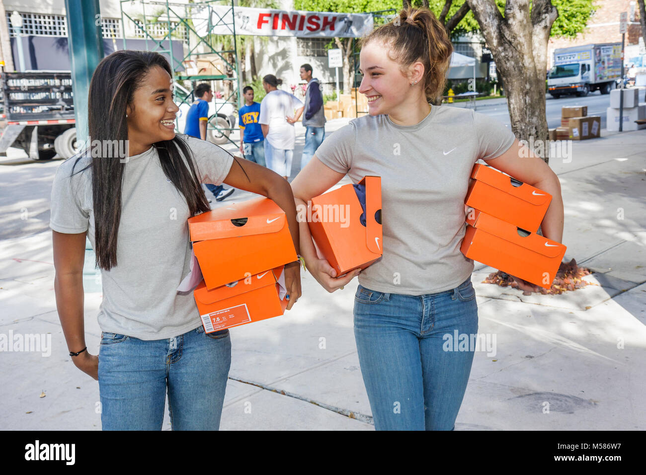 Carnaval 8K Run preparation community event teen volunteers student Black female girl - Stock Image