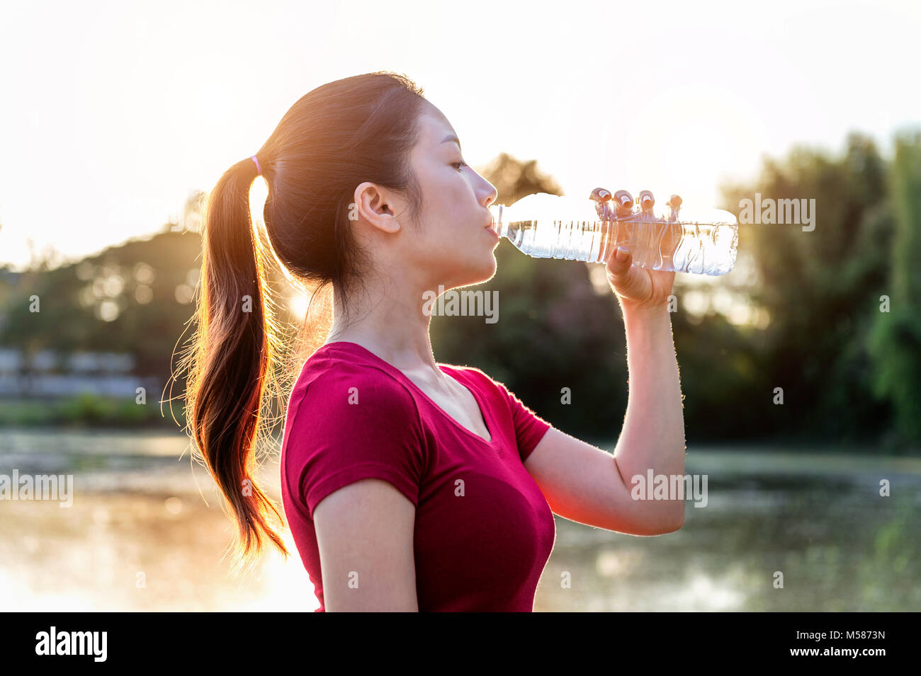 Sporty woman drinking water on sunlight. Stock Photo
