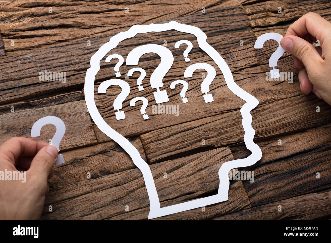 Cropped image of businessman holding question marks by paper head outline at wooden table - Stock Image