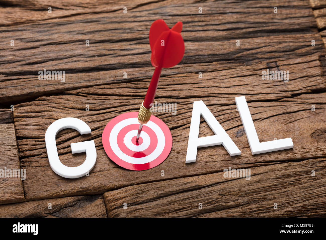 High angle view of red arrow in dartboard with goal text on wooden table - Stock Image