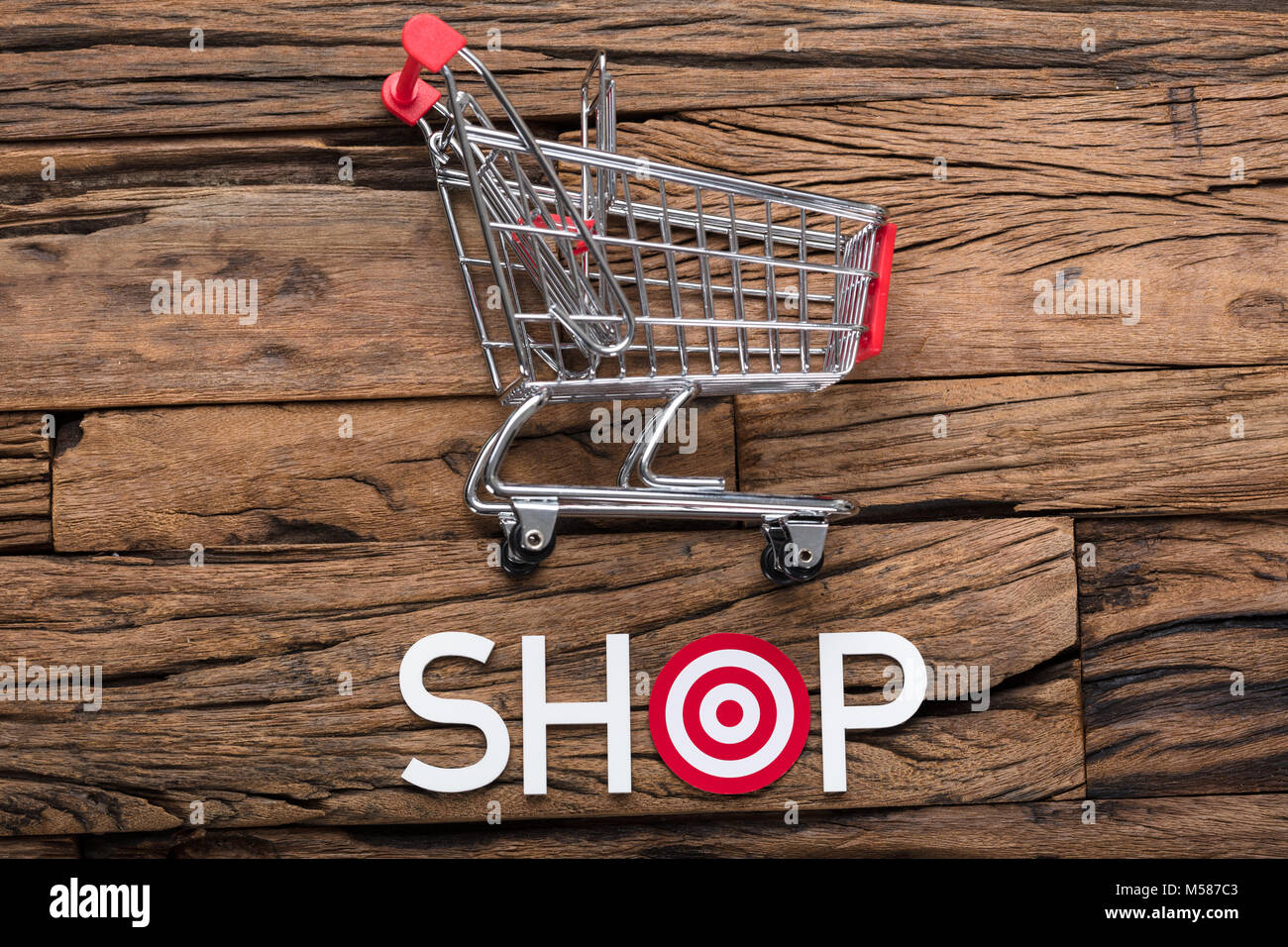 High angle view of shop text with dartboard on wooden table - Stock Image