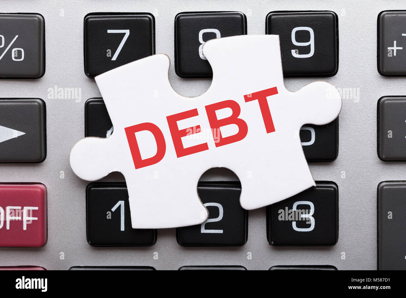 Directly above shot of jigsaw puzzle piece with debt text on calculator - Stock Image