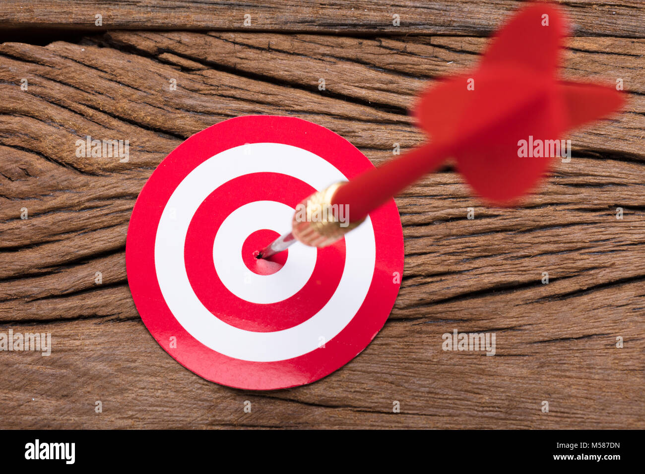Closeup of red arrow in dartboard on wooden table - Stock Image