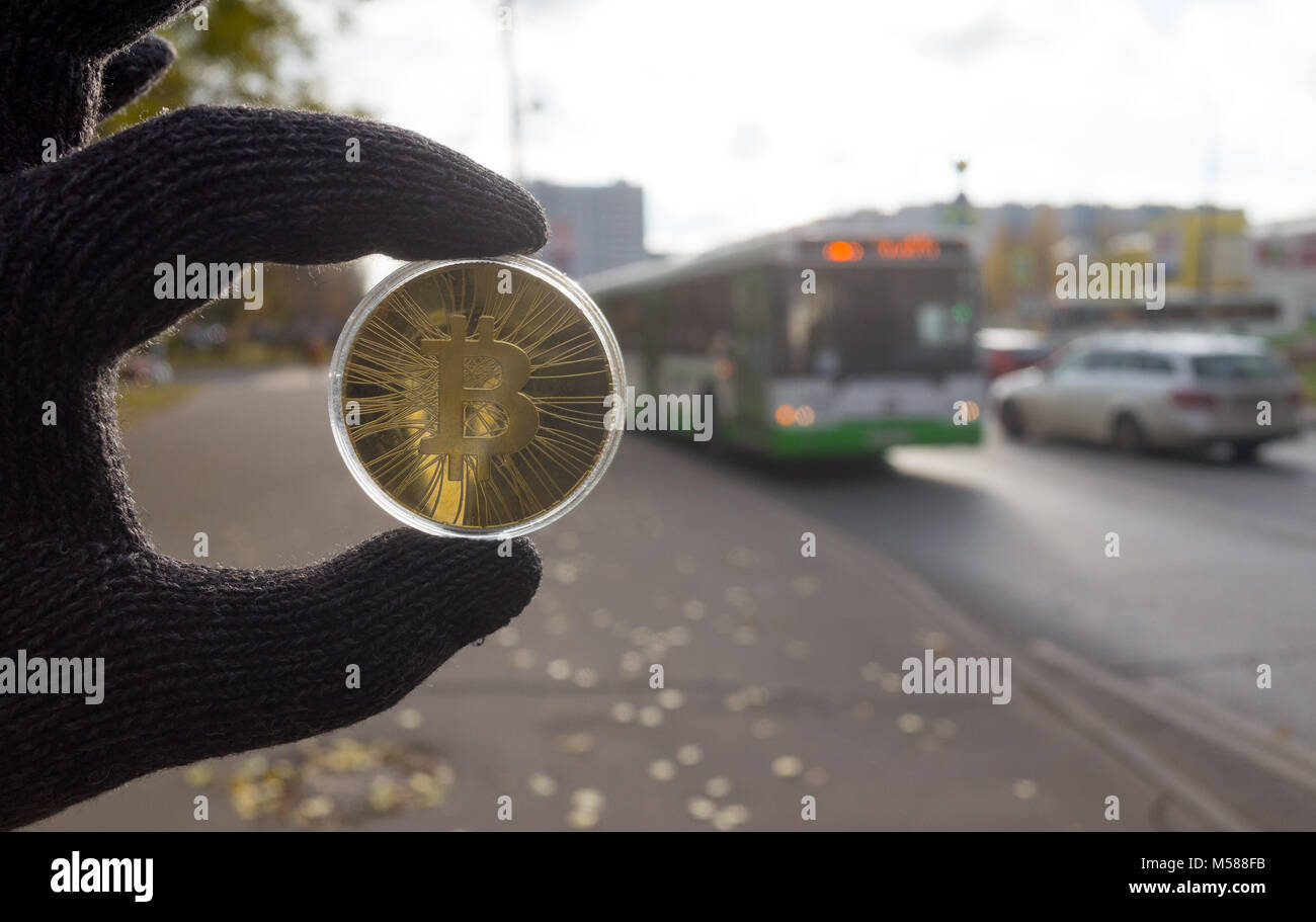 Gold bitcoin on the background of automobile traffic - Stock Image