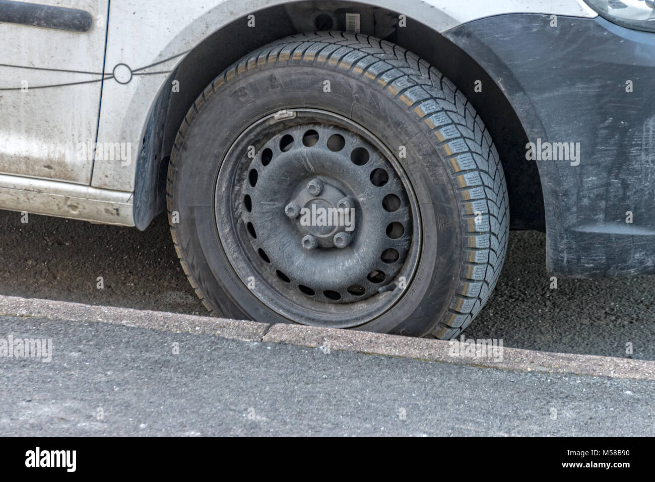 Worn winter car tire at a parked car - Stock Image
