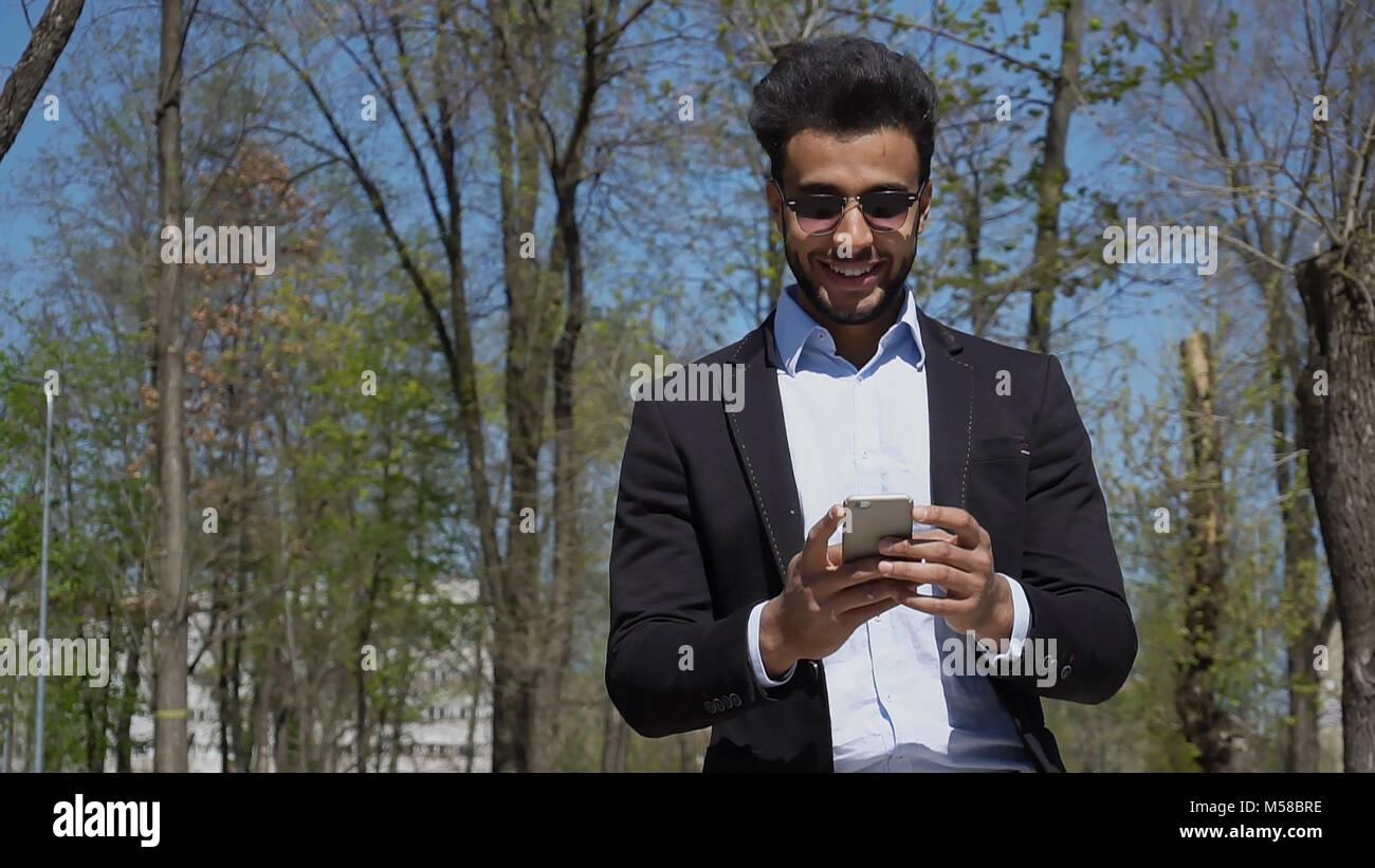 Arabian writer checking e-mail on phone.  - Stock Image