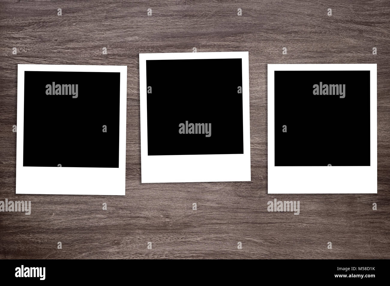 three blacked-out instant photo print templates on wooden background Stock Photo