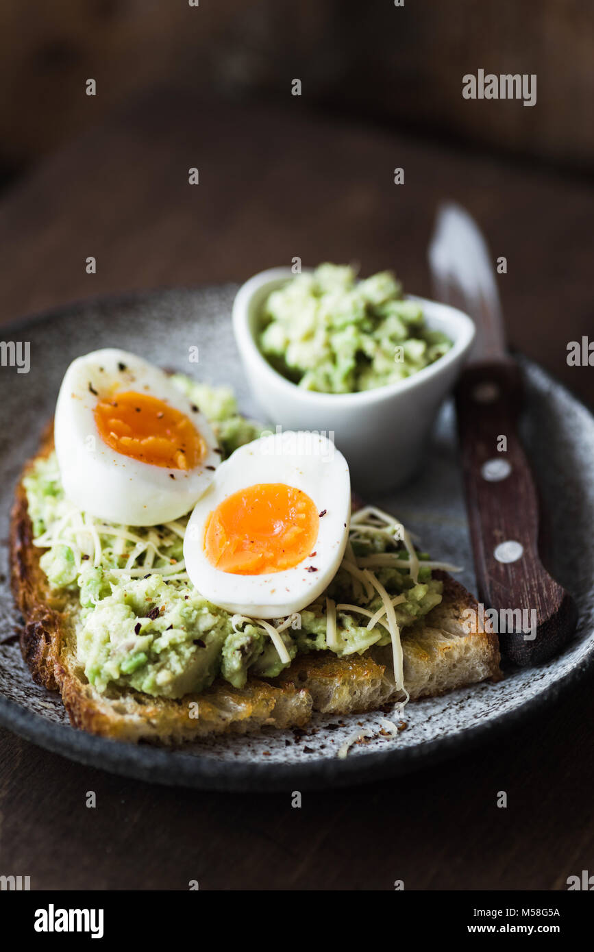 Mashed avocado, egg and cheese on toasted bread. Healthy lifestyle, healthy eating concept. Dark food photo, selective - Stock Image