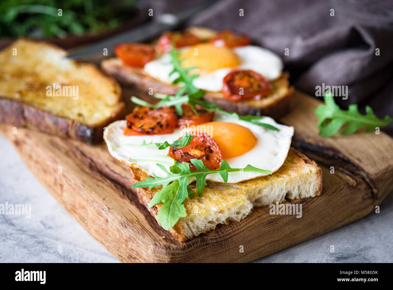 Healthy breakfast toast with egg, roasted tomato and arugula on rustic wooden cutting board. Closeup view - Stock Image