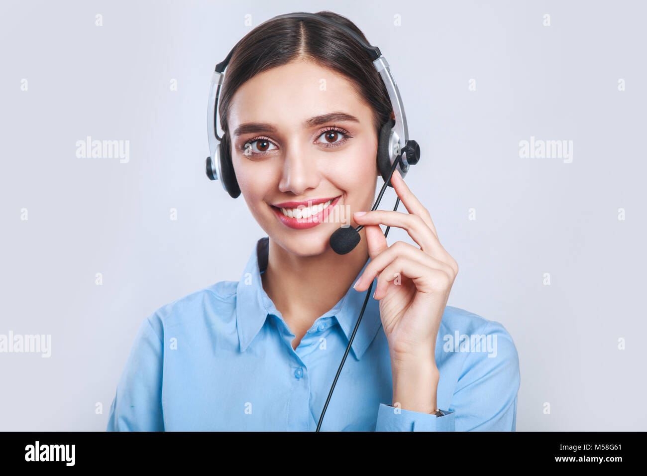 Woman customer service worker, call center smiling operator with phone headset - Stock Image