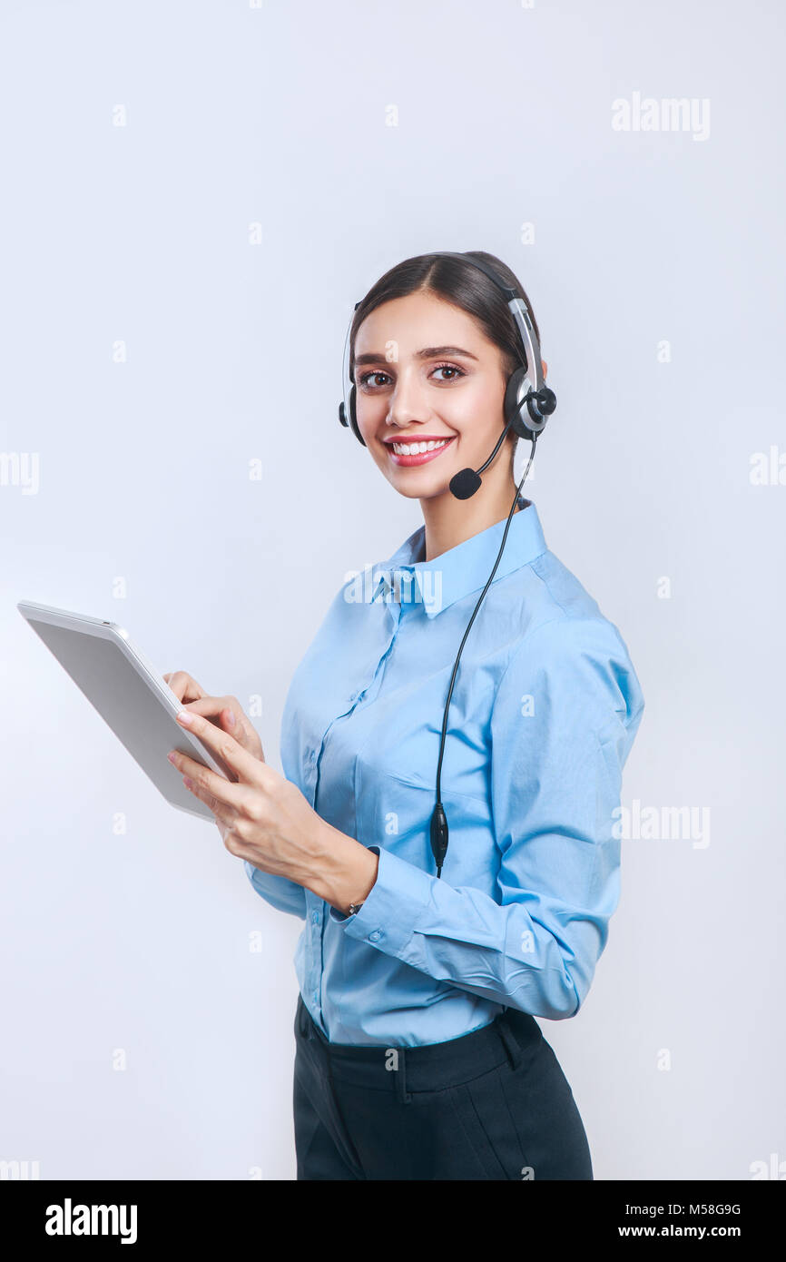 Female customer support operator with tablet. Call center operator - Stock Image