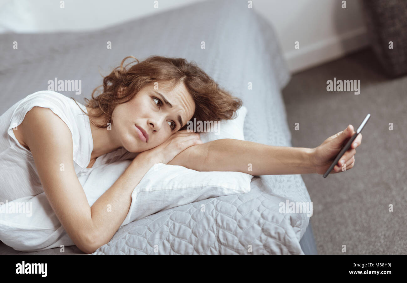 Depressed woman lying on bed and looking at smartphone - Stock Image
