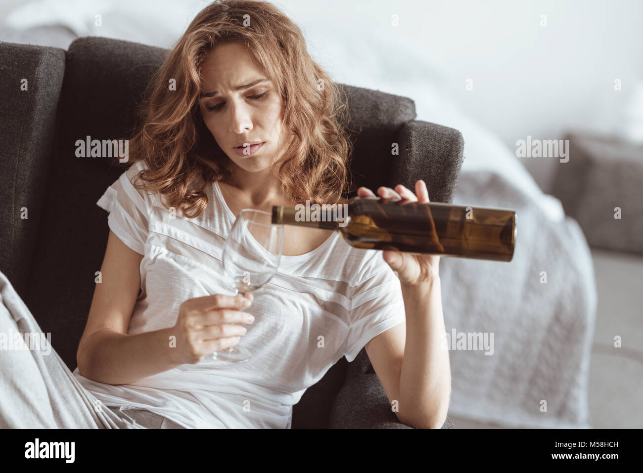 Stressed woman pouring wine at home - Stock Image