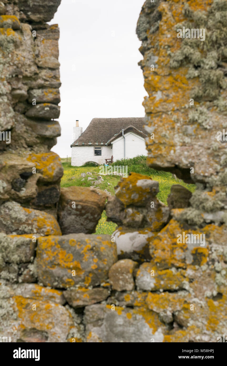 White stone thatched cottage of Howmore Gatliff Hostel,photographed fro nearby 13th century monastery Isle of South - Stock Image