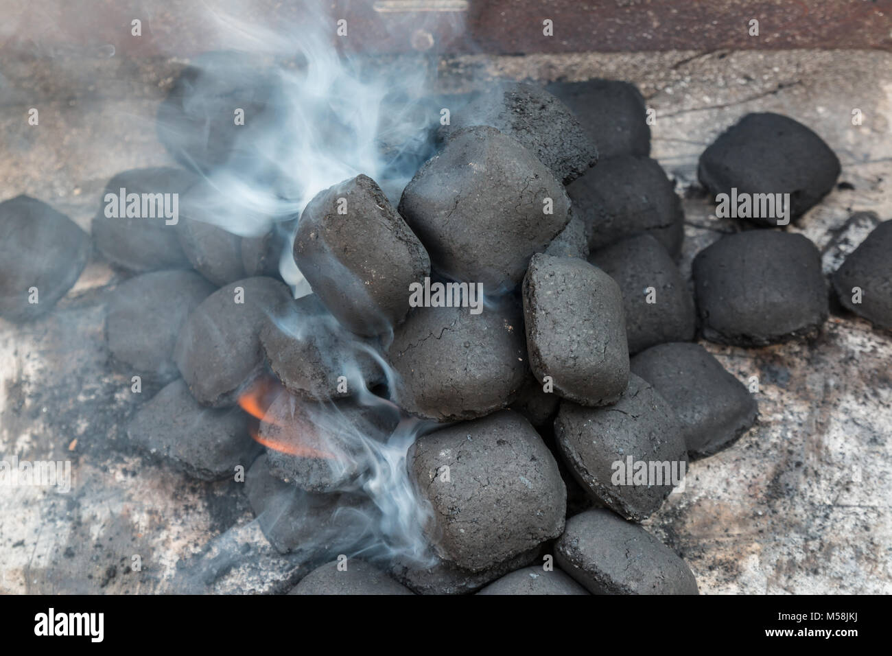 Fire up the grill with briquettes with a lot of smoke Stock Photo