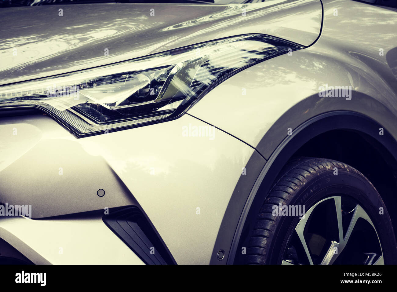 Concept shot of headlamp and part of modern crossover car - Toyota CH-R. Stock Photo