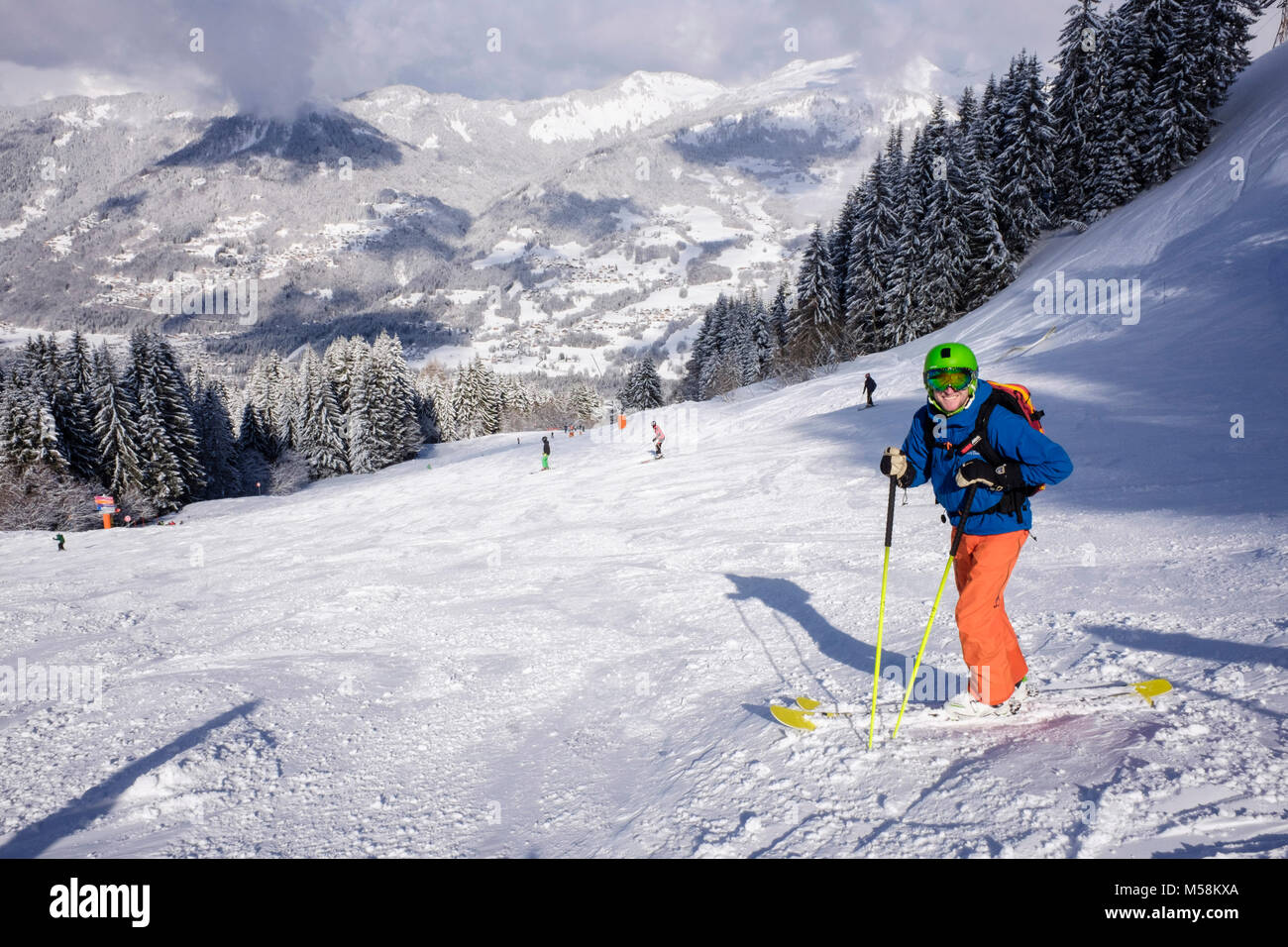 Male skier in French Alps in winter snow skiing on red route ski slope Grand Cret to Vercland, Samoens, Haute Savoie, - Stock Image