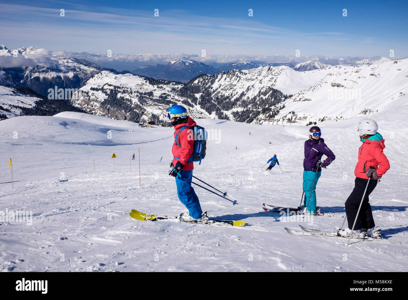 Skiers skiing on red route ski slope in le Grand Massif ski area in French Alps in winter snow above Flaine, Haute - Stock Image