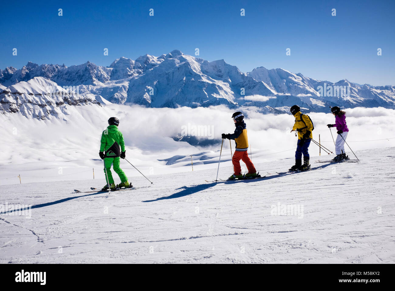Skiers skiing on snow ski slope with Mont Blanc as backdrop in Grand Massif in French Alps. Tetes des Lindars Flaine - Stock Image