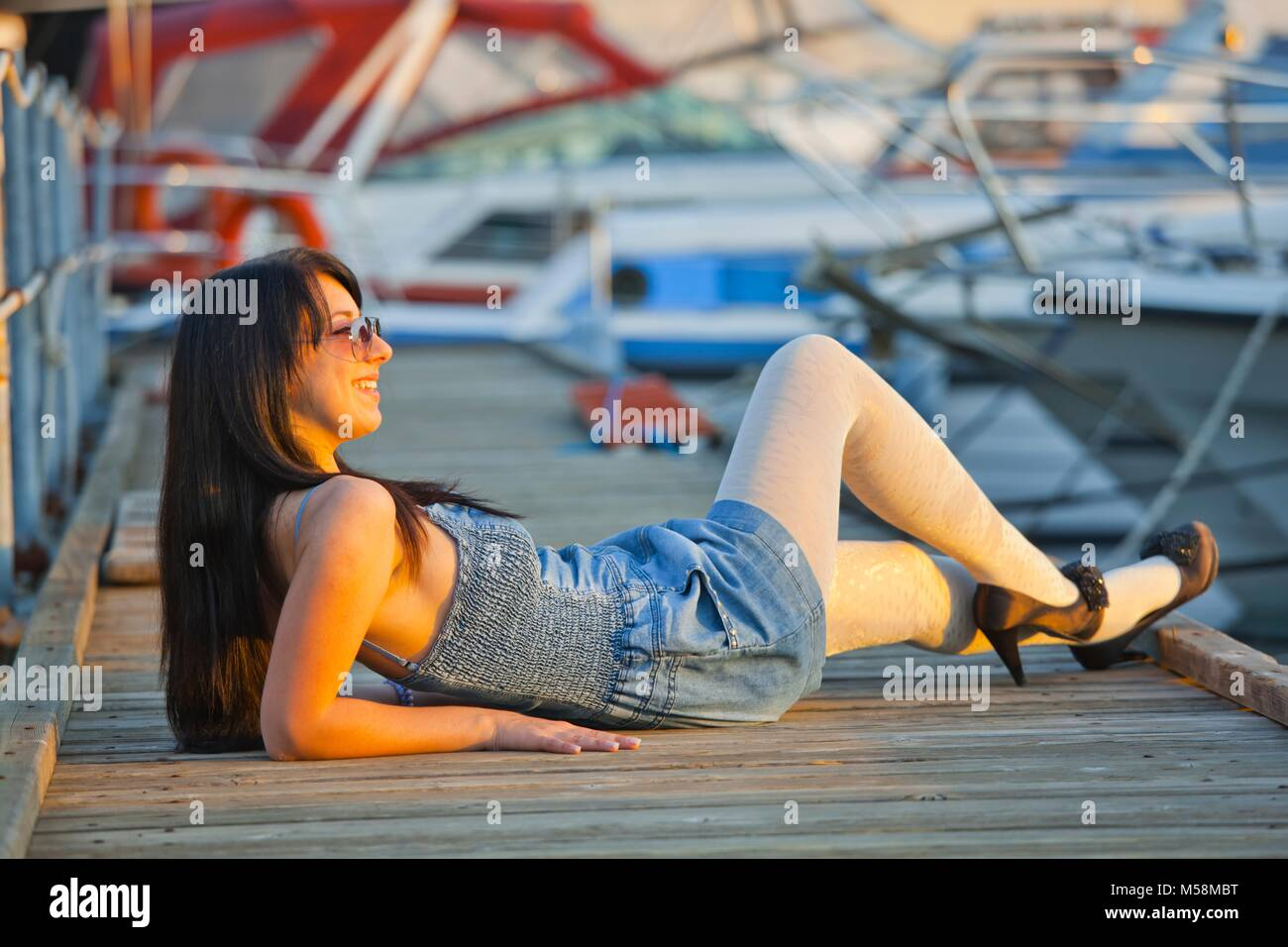 Young woman legs heels lying accros peer and smiling away wearing White tights pantyhose beauty Stock Photo